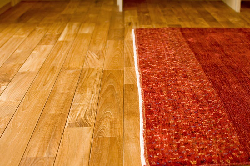マットとの色のコントラストが美しい天然木材のチーク・ユニ フローリング