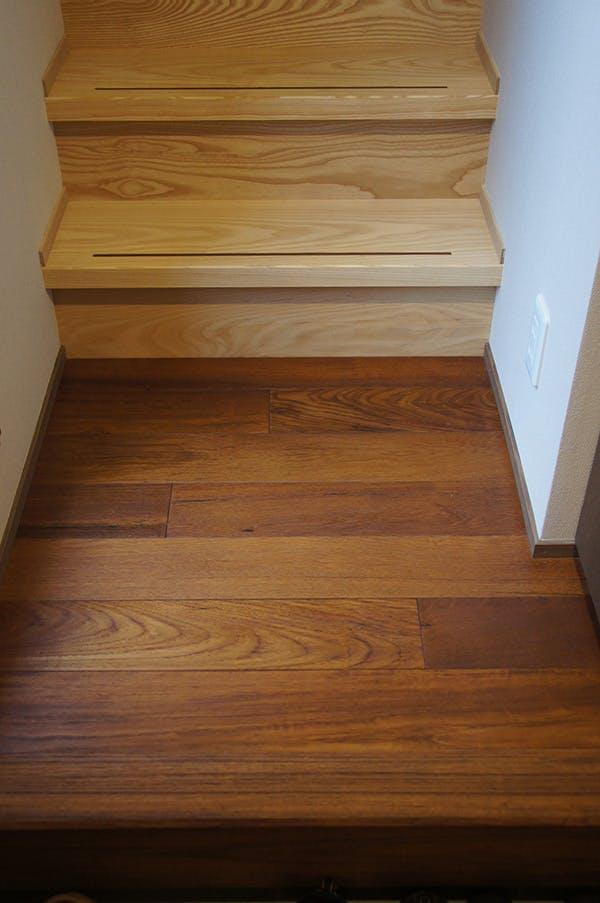 チークの床材と階段材はホワイトアッシュを。天然木材の木目の強い樹種同士、色のコントラストが見事です!